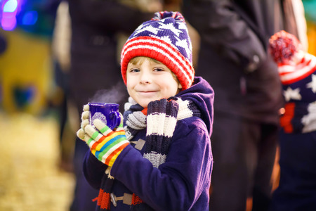 Little adorable kid boy with cup of steaming hot chocolate or children punch. Happy child on Christmas market in Germany. Traditional leisure for families on xmas Archivio Fotografico