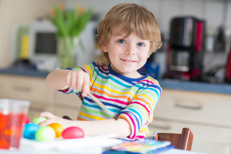 Happy kid boy of 4 years coloring eggs for Easter holiday in domestic kitchen, indoors. Child having fun and celebrating feast. Stock Photo