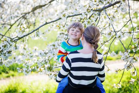 arbol de manzanas: Ni�o feliz y sus abrazos madre en jard�n floreciente cerezo en primavera. Familia feliz que celebra d�a de la madre. Foto de archivo