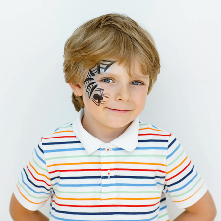 spiderman: Beautiful little kid boy with face painted with a spider web, on a birthday party. happy child having fun.