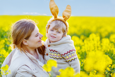 ear: Little toddler boy  in Easter bunny ears  and his mother having fun, celebrating traditional Easter holiday. In blooming yellow rape flower field, outdoors, on warm spring day. Happy family.