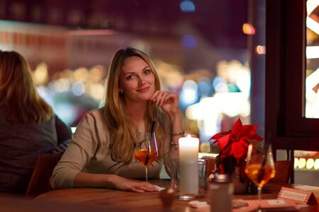 cocktails: Young beautiful woman drinking champagne cocktail after work in an indoor cafe and restaurant in Berlin, Germany. Christmas market lights on background. Happy girl dreaming on evening or night. Stock Photo