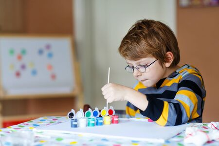 children hands: Portrait of happy preschool kid boy with glasses at home making homework. Little child drawing with colorful watercolors and gouache, indoors. School, education concept Stock Photo