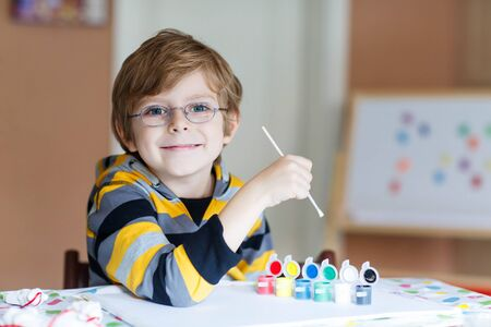 smile close up: Portrait of happy preschool kid boy with glasses at home making homework. Little child drawing with colorful watercolors and gouache, indoors. School, education concept Stock Photo