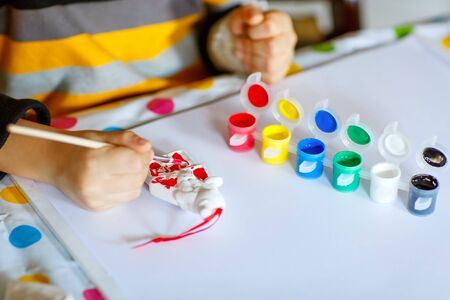 smile close up: Hands of cute happy preschool kid boy with glasses at home making homework. Little child drawing with colorful watercolors and gouache, indoors. School, education concept