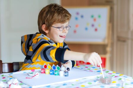 smile close up: Funny preschool kid boy with glasses having fun with coloring. Little child drawing with colorful watercolors and gouache, indoors. School, education concept