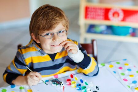 smile close up: Portrait of funny preschool kid boy with glasses and broken hand drawing. Little child having fun with colorful watercolors and gouache, indoors. School, education concept Stock Photo