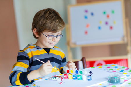children hands: Portrait of adorable preschool kid boy with glasses at home making homework. Little child drawing with colorful watercolors and gouache, indoors. School, education concept Stock Photo