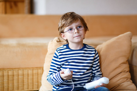 depending: Cute little blond kid boy playing with a video game console. Child having fun at home. Addiction concept