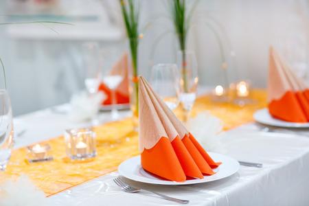 ramo de flores: Juego de mesa para la boda o partido del acontecimiento. Elegante y de lujo de la decoraci�n de color naranja suave con flores, cubiertos de plata, vasos de vino, servilleta textil.