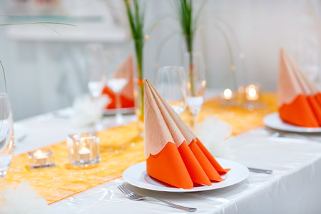 bouquet fleurs: Table set  for wedding or event party. Elegant and luxury decoration in soft orange with flowers, silver cutlery, wine glasses, textile napkin.