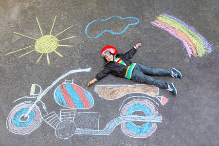 having fun: Happy kid boy in race helmet having fun with motorcycle picture drawing with colorful chalks. Children, lifestyle, fun concept. Creative leisture for kids