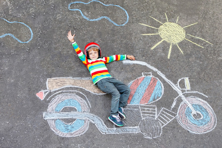 having fun: Creative leisure for children: Adorable little child of four years in helmet having fun with motorcycle picture drawing with colorful chalks. Children, lifestyle, fun concept. Stock Photo