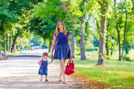 mignonne petite fille: Beautiful young mother and her little daughter walking in summer park. Woman and cute kid girl spending time together. Happy family of two on warm sunny day Banque d'images