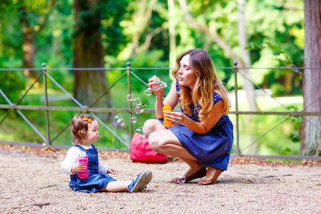 mignonne petite fille: Happy young mother and adorable toddler girl blowing soap bubbles and having fun together, outdoors. Woman and daughter playing on warm sunny day in park