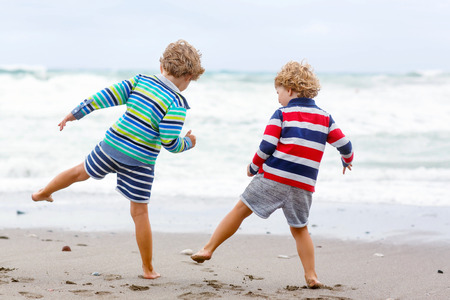 Two little blond kid boys having fun on lonely ocean beach. Friends, Children playing and running on stormy windy bad weather day.