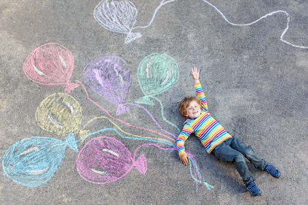 cute little boy: Cute little kid boy playing and flying with colorful balloons picture drawing with chalk. Creative leisure for children outdoors in summer, celebrating birthday