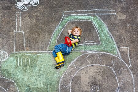 having fun: Happy little boy having fun with tractor picture drawing with chalk. Stock Photo
