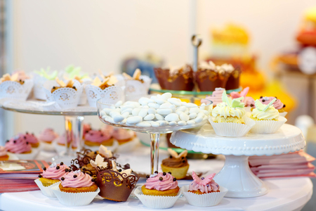 sweet table: Elegant sweet table with cupcakes, cake pops and candy on dinner or event party