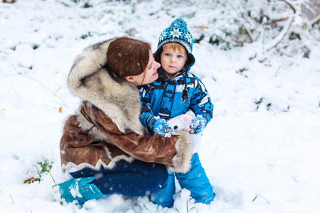 having fun in the snow: Winter portrait of kid boy and mother in colorful clothes, outdoors during snowfall. Active outoors leisure with children in winter on cold snowy days. Happy woman and son having fun with snow in forest