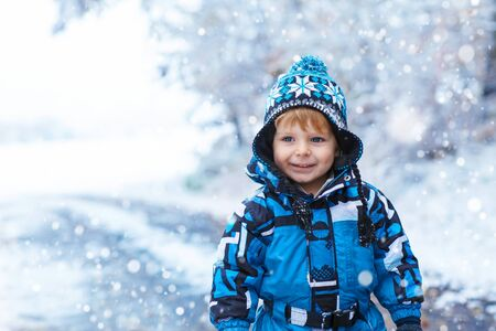 Winter portrait of kid boy in colorful clothes, outdoors during snowfall. Active outoors leisure with children in winter on cold snowy days. Happy toddler child having fun with snow in forest Stock Photo