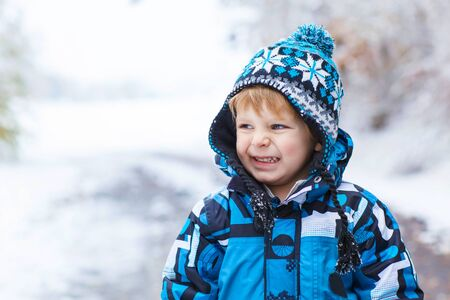 having fun in the snow: Winter portrait of funny kid boy in colorful clothes, outdoors during snowfall. Active outoors leisure with children in winter on cold snowy days. Happy toddler child having fun with snow in forest Stock Photo