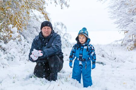 having fun in the snow: Winter portrait of kid boy and father in colorful clothes, outdoors during snowfall. Active outoors leisure with children in winter on cold snowy days. Happy man and son having fun with snow in forest Stock Photo
