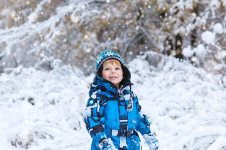 having fun in the snow: Winter portrait of kid boy in colorful clothes, outdoors during snowfall. Active outoors leisure with children in winter on cold snowy days. Happy toddler child having fun with snow in forest Stock Photo