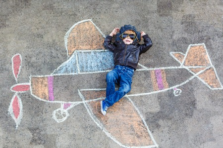 people having fun: Creative leisure for children: Funny little child of four years having fun with airplane picture drawing with chalk. Stock Photo
