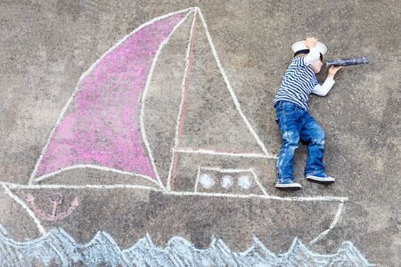 childhood: Creative leisure for children: Funny little boy of four years having fun with ship or boat picture drawing with chalk. Stock Photo