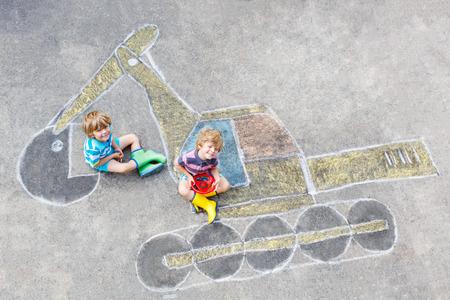 少し満足している 2 つのカラフルなチョークでショベル絵かき持つ楽しみの男の子を子供します。夏の屋外での子供のための創造的なレジャー。 写真素材