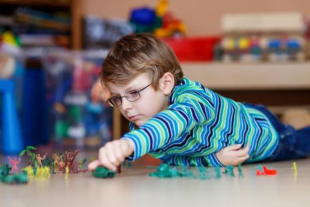 gafas: Lindo ni�o rubio jugando con un mont�n de peque�os soldados de juguete, de interior. Ni�o chico activo con gafas vistiendo camisa colorido y la diversi�n en casa o en la guarder�a. Foto de archivo