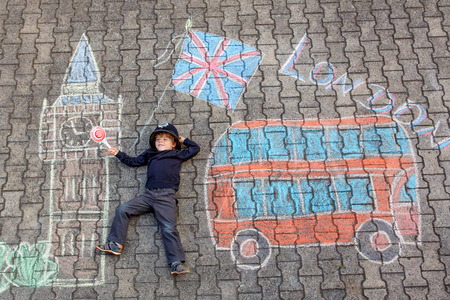 friends having fun: Happy little kid boy in british policeman uniform having fun with London picture drawing with colorful chalks. With Big Ben, Union Jack and red bus.