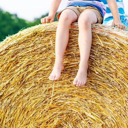 warm shirt: Legs of a kid traditional German bavarian clothes, leather shorts and check shirt. Child sitting on hay stack or bale and dreaming. Active outdoors leisure with children on warm summer day.