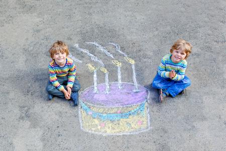Twee gelukkige kleine kinderen plezier hebben met een grote verjaardagstaart afbeelding tekenen met kleurrijke krijtjes. Creatieve vrijetijdsbesteding voor kinderen buiten in de zomer. Jongens, vrienden vieren verjaardag