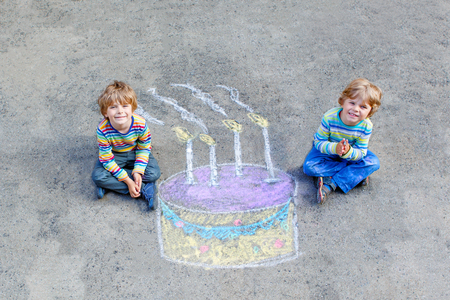Two happy little kids having fun with big birthday cake picture drawing with colorful chalks. Creative leisure for children outdoors in summer. Boys, friends celebrating birthday party