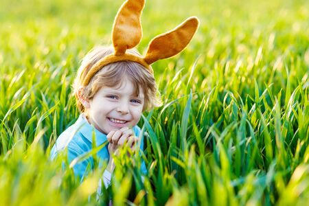 animal ear: Adorable little boy with Easter bunny ears playing in green grass on sunny spring day. Happy child celebrating Easter holiday. Family, holiday, spring , carefree childhood concept.