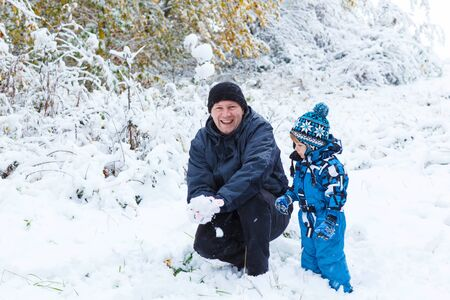 outoors: Winter portrait of kid boy and dad in colorful clothes, outdoors during snowfall. Active outoors leisure with children in winter on cold snowy days. Happy man and son having fun with snow in forest Stock Photo