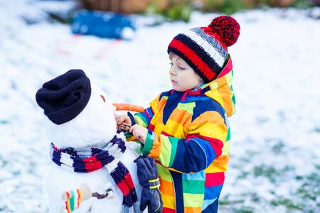 having fun in the snow: Funny kid boy making a snowman and eating carrot, playing and having fun with snow on cold day. Active outdoors leisure with children, kids in winter. Stock Photo