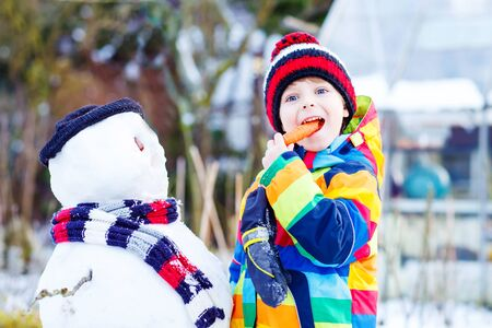 having fun in the snow: Beautiful little kid boy making a snowman and eating carrot. child playing and having fun with snow on cold day. Active outdoors leisure with kids in winter. Stock Photo