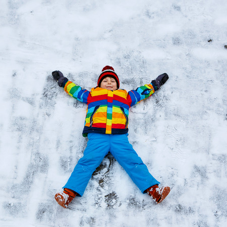 Cute little kid boy in colorful winter clothes making snow angel, laying down on snow. Active outdoors leisure with children in winter. Happy child with warm hat, hand gloves, winter fashion Stock Photo