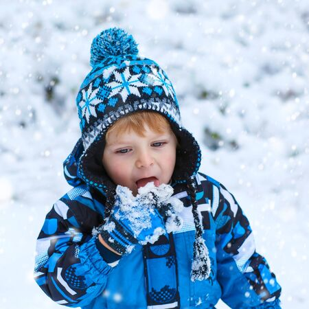outoors: Winter portrait of cute kid boy in colorful clothes, outdoors during snowfall. Active outoors leisure with children in winter on cold snowy days. Happy toddler child having fun with snow in forest