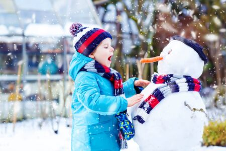having fun in the snow: Funny little kid boy making a snowman and eating carrot. child playing and having fun with snow on cold day. Active outdoors leisure with kids in winter.