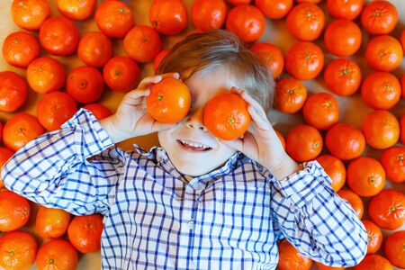citrus family: Adorable little kid boy with mandarin oranges background. Happy smiling child having fun with lot of fruits. Healthy food, eating and lifestyle concept.