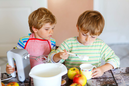 cake mixer: Two little kid boys baking apple cake in domestic kitchen. Adorable siblings having fun with working with mixer, eggs and fruits. Twins helping at home