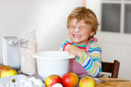 cake mixer: Beautiful funny blond little kid boy baking apple cake and muffins in domestic kitchen. Happy child having fun with working with mixer, flour, eggs and fruits at home.