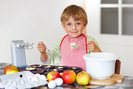 cake mixer: Cute funny blond preschool kid boy baking apple cake and muffins in domestic kitchen. Happy child having fun with working with mixer, flour, eggs and fruits at home. Stock Photo