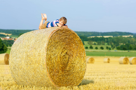 warm shirt: Happy little kid boy in traditional German bavarian clothes, leather shorts and check shirt. Child lying on hay stack or bale and dreaming. Active outdoors leisure with children on warm summer day. Stock Photo