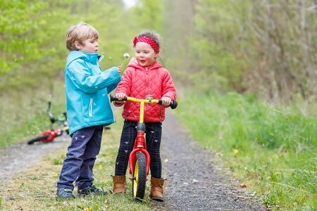 boy lady: Two little cute smiling kids in bright jackets walking together in a forest on a rainy day with bikes. Friendship between siblings. Happy family concept Stock Photo