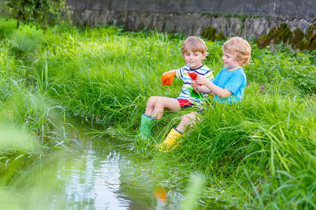 brother: Two little friends playing with paper boats by a river on warm and sunny summer day. Active leisure for children. Kid boys having fun together outdoors. Stock Photo